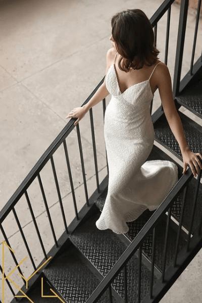 Brud går ned af trappe i en tætsiddende brudekjole