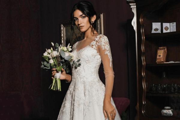 Kvinde i en Kayla Dresses brudekjole med blondedetaljer på skulder